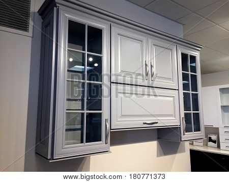 Kitchen cabinet with glass doors. Contemporary full overlay wall kitchen cabinets. Handels on kitchen cabinet. Kitchen cabinet design with crown molding. Gray wooden kitchen cabinet in showroom.