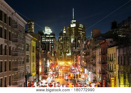 NEW YORK CITY - FEBRUARY 24th 2017: The colorful streets of Chinatown light up with cars shops and people during a busy weekend night in downtown Manhattan New York City on February 24th 2017.