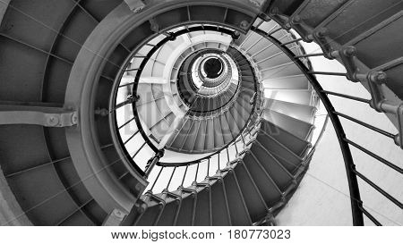 Interior view looking up a black and white spiral staircase