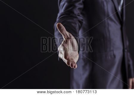 closeup of a businessman extends his hand forward for a handshake.photo on a black background and has space for your text.t