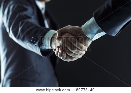 closeup of a business handshake partners.photo on a black background and has space for your text.