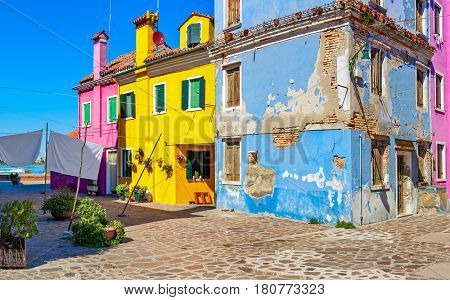 Small courtyard surrounded by old colorful houses on Burano island in Venice, Italy.