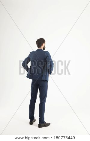 confident businessman in a business suit standing with his back to the camera.the photo has a empty space for your text