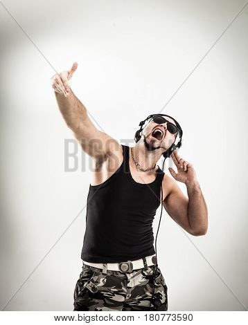 DJ - rapper in headphones takes the rap and break dancing dance on a light background.the photo has a empty space for your text