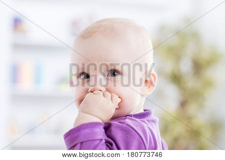 happy one year old baby girl on a background of bright children's room.the photo has a empty space for your text.
