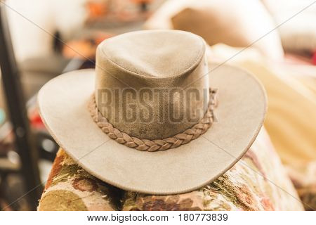 Leather cowboy hat resting on an old couch.