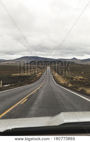 Two-lane highway trailing off into the distance. Driver's point of view on rural highway in Oregon USA.