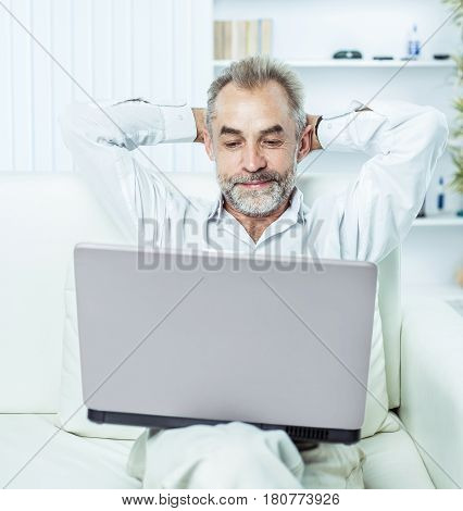 businessman working on laptop sitting on sofa in modern office. the photo has a empty space for your text