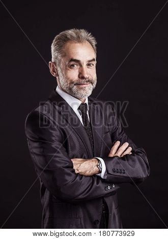 successful businessman with arms crossed on black background.the photo has a empty space for your text