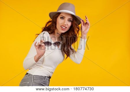 Smiling woman in spring hat  and white shirt looking at camera , Three quarter length studio shot on yellow background.