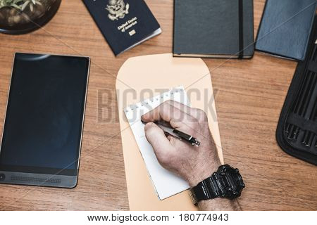 Man writing on a note pad with envelope passport tablet check book and other related accessories nearby.