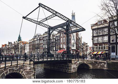 AMSTERDAM (NETHERLANDS) - CIRCA JANUARY 2017: Drawbridge or bascule bridge on canal with metal mechanism side view in cloudy day - Amsterdam, Netherlands