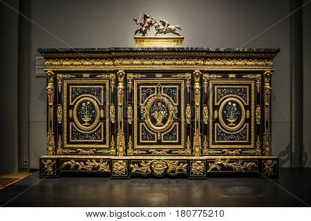 AMSTERDAM (NETHERLANDS) - CIRCA JANUARY 2017: Antique inlaid and ormolu Dutch cabinet decorated with vases of flowers and topped with an equestrian sculpture