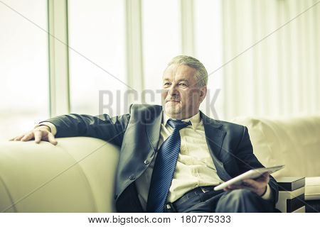 lawyer with digital tablet sitting on the sofa in the private office. the photo has a empty space for your text