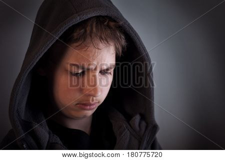 Problems of teenagers, Sad child sitting in a dark room thinks