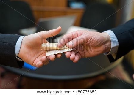 Man taking a bribe from another one