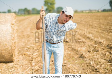 Farmer suffering from backache while working in his field
