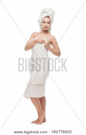 Beautiful smiling young woman standing in bath towel. Isolated on white background. Copy space.