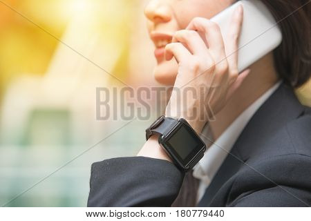 Businesswoman Talking On Phone And Wrist Smartwatch
