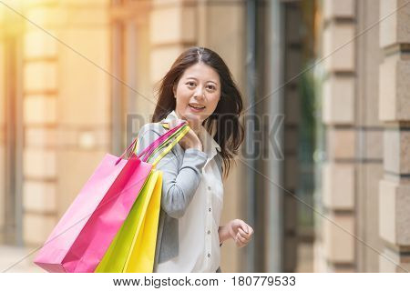 Smiling Young Woman With Shopping Bags Over Street