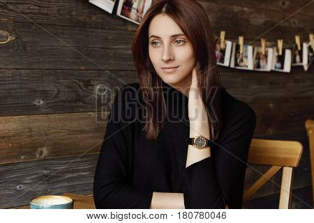 Indoor Shot Of Attractive Pensive Young European Female Enjoying Her Leisure Time Alone Drinking Tea
