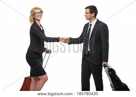 Beautiful business lady and handsome businessman standing with hand luggage travel cases shaking hands. Isolated on white background. Copy space.