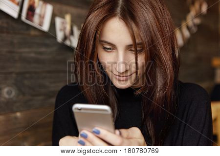 Quick Message To Friend. Attractive Brunette European Woman Using Photo Editing Application On Her M