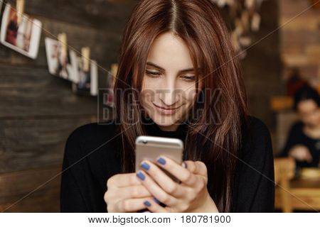 Happy Cute Young Female With Long Dark Hair Messaging Friends Online Using Modern Smartphone Device