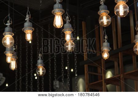 Lighting on the chandelier in the lamplight light bulbs hanging from the ceiling lamps on the dark background .Coffee Shop Decoration .