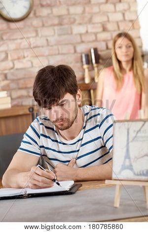 Young man sitting at desk, writing at home.