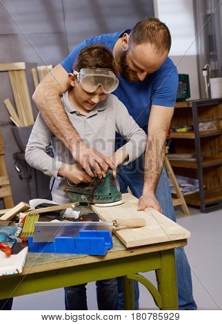Diy father teaching son the use of jigsaw in workshop.