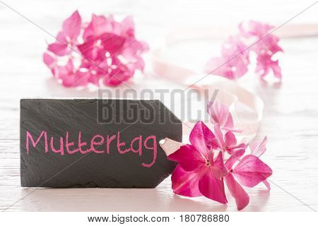 Plate Of Slate With German Text Muttertag Means Mothers Day. Spring Flower Blossom Of Hydrangea. Shiny White Wooden Background
