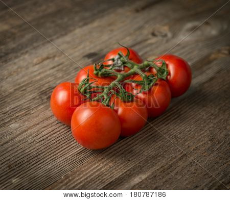 Red ripe fresh tomatoes connected to each other on the wooden table, closeup