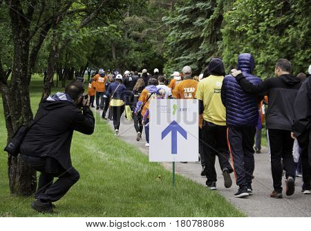 Laval, Quebec - June 12, 2016 - A shot from the back of a photographer taking pictures of people walking down a path at the Junior Diabetes Walk in Laval, Quebec on a bright overcast day in June.
