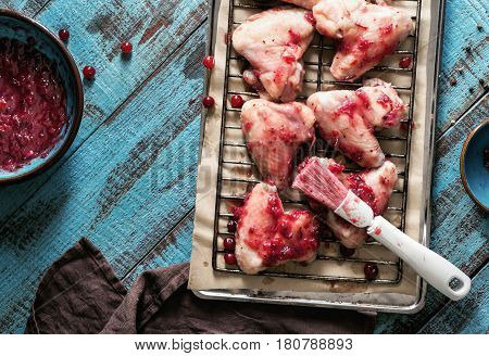 Healthy food. Close up raw chicken wings in cranberry sauce on a baking tray on a blue wooden table with copy space top view