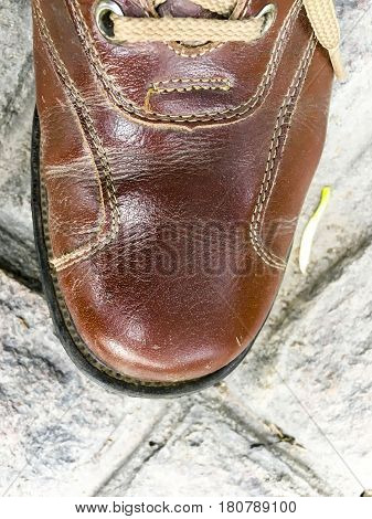 Closeup of brown leather lace shoe on a rocky floor background
