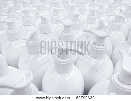White unlabeled liquid soap bottles in supermarket repeating pattern of large group of plastic containers for hygiene product