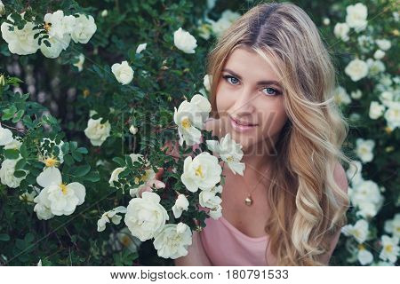 Beautiful happy woman with long curly hair smells white roses flower outdoors. Closeup portrait of sensual blonde girl face. Vintage toning.