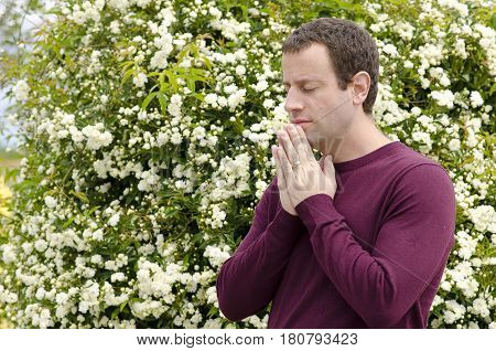 Side profile of man praying in front of a flowering bush.