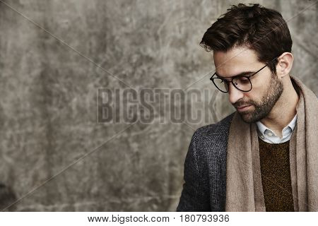 Studious man in spectacles and scarf studio