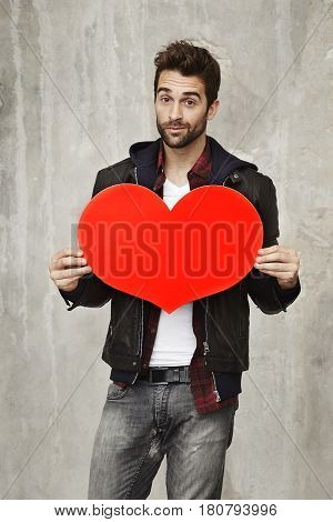 Romantic dude in love holding love heart portrait
