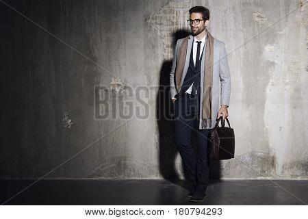 Cool Businessman in shadowy studio looking away
