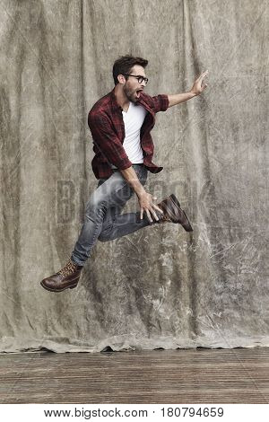 Cool Jumping dude in jeans in studio