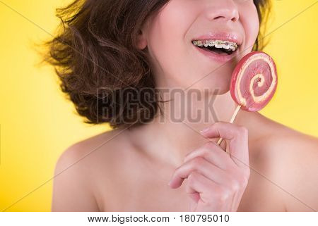 Young woman with multi-colored bracket system and candy posing on yellow background. Dental concept