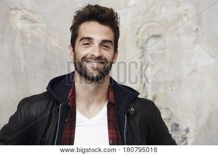 Smiling stubble man in leather jacket portrait