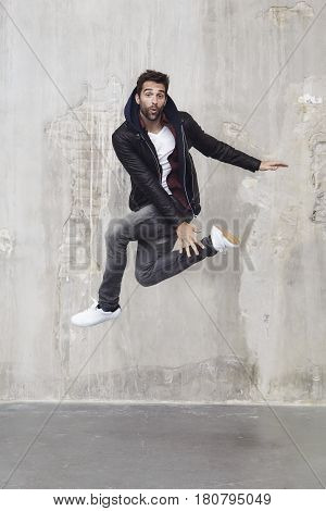 Cool Leaping lad in leather jacket studio portrait