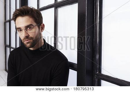 Bookish dude in black sweater and glasses portrait