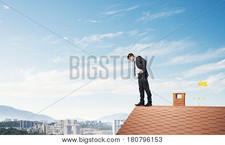 Young businessman standing on edge of house brick roof and looking down. Mixed media