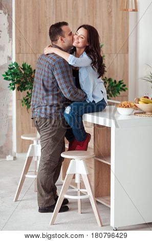 Beautiful young passionate couple is smiling and hugging before having sex in kitchen at home.
