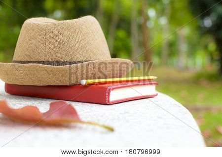 Concept holiday,Notebook and pencil with hat on white table in public park.